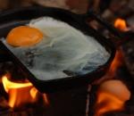 Gusseisernes Kochgerät am und im Feuer